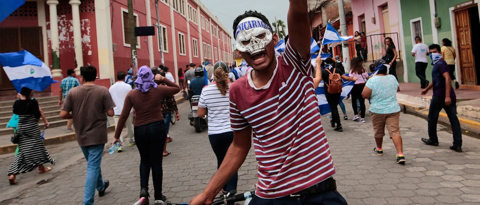 A masked demonstrator takes part in a protest against Nicaraguan President Daniel Ortega's government in Granada
