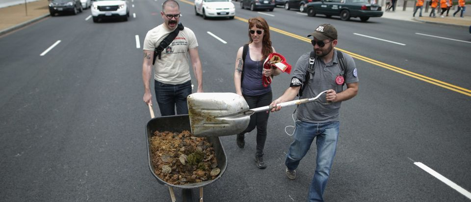 "WASHINGTON, DC - APRIL 22: (L-R) Farhad Ebrahimi of Boston, Virgina Leavell of the District of Columbia and David Turnbull of San Francisco scoop horse manure up from the middle of Independence Avenue after members of the Cowboy and Indian Alliance rode horseback while demonstrating against the proposed Keystone XL pipeline April 22, 2014 in Washington, DC. As part of its ""Reject and Protect"" protest, the Cowboy and Indian Alliance is organizing a weeklong series of actions by farmers, ranchers and tribes to show their opposition to the pipeline. (Photo by Chip Somodevilla/Getty Images)"