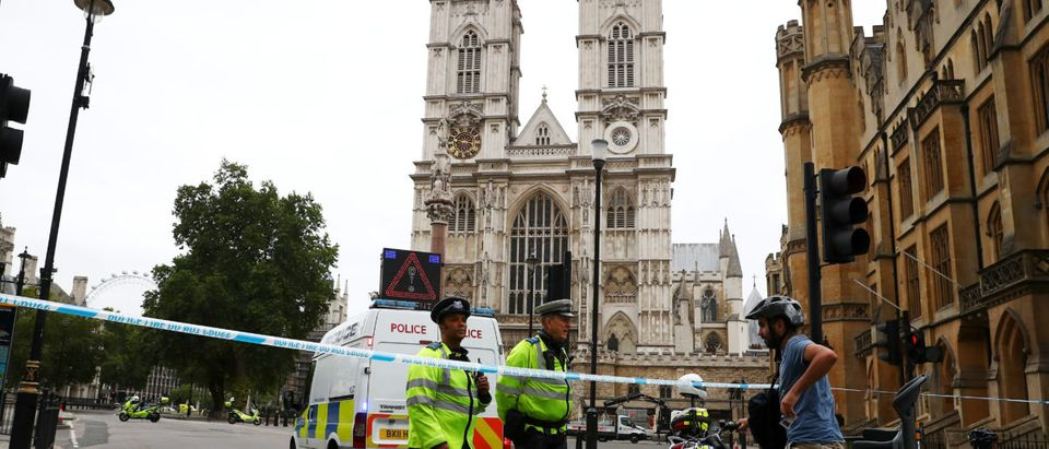 Police officers stand at a cordon after a car crashed outside the Houses of Parliament in Westminster, London