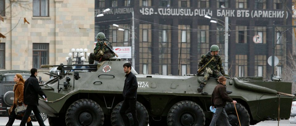 People walk past armoured vehicle in central Yerevan