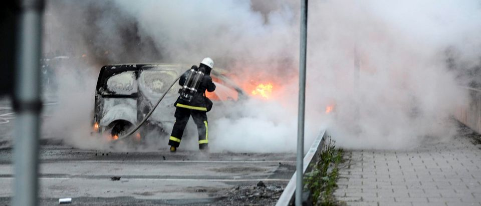 FILE PHOTO: Firemen extinguish a burning car in the suburb of Rinkeby after youths rioted in several different suburbs around Stockholm
