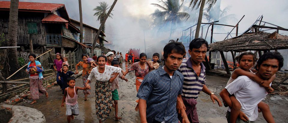 FILE PHOTO: Rohingyas run away from a fire that was set to a part of Sittwe, during clashes