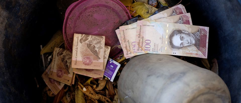 Venezuelan 100 bolivar notes thrown by people in a trash bin are seen at a gas station of the Venezuelan state-owned oil company PDVSA in Caracas, Venezuela August 20, 2018. REUTERS/Marco Bello - RC1820029ED0