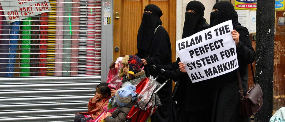 Women hold placards during a march and rally organised by British Islamist Choudary in east London