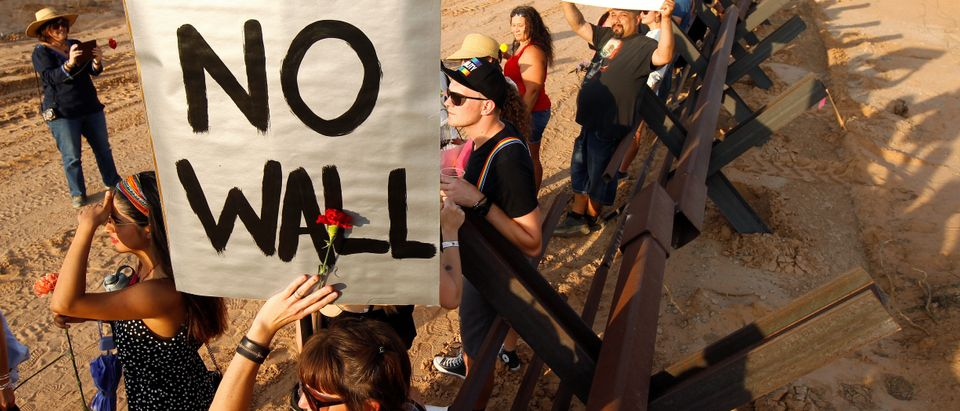 Demonstrators hold up placards during a protest against the border wall and the militarization of the border at a new section of the bollard wall in Santa Teresa as seen from the Mexican side of the border in San Jeronimo
