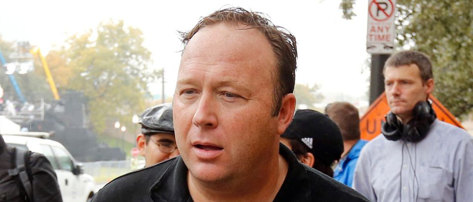 FILE PHOTO: Conspiracy theorist, radio talk show host and Infowars.net founder Alex Jones walks up Elm Street past the spot where U.S. President John F. Kennedy was assassinated in Dealey Plaza in 1963 one day before commemorations of the 50th anniversary of the assassination in Dallas, Texas, U.S., November 21, 2013. REUTERS/Jim Bourg/File Photo