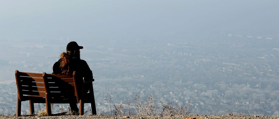 A man sits on a park bench and looks over the smog filled Salt Lake Valley in Draper