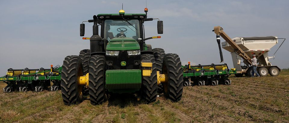 A soybean seeding tractor is replenished with soybean seeds in a field in Gideon, Missour