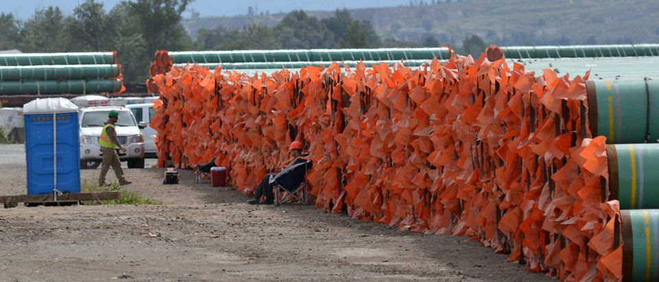 Workmen rest amid steel pipe to be used in the pipeline construction of the Trans Mountain Expansion Project at a stockpile site in Kamloops