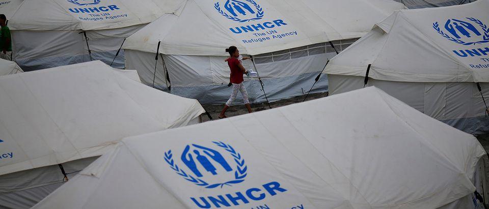 Venezuelan migrants walk between the tents in UNHCR shelter in Boa Vista