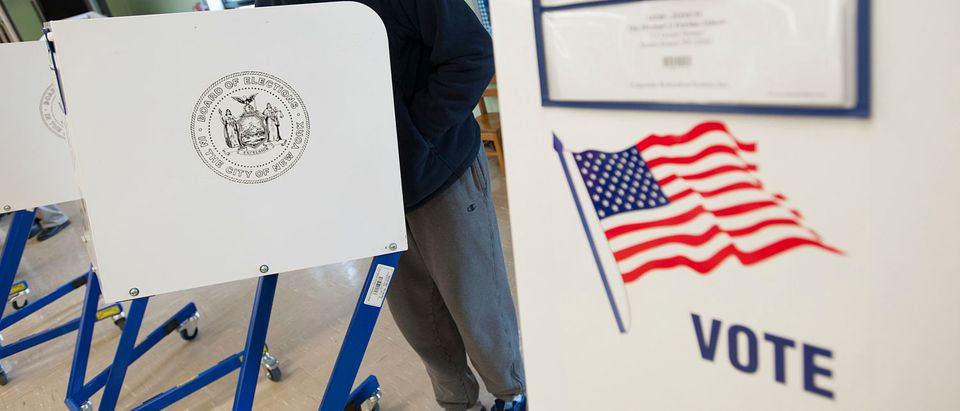 A voter casts his ballot behind a ballot booth during the U.S. presidential election at a polling station in the Staten Island Borough of New York