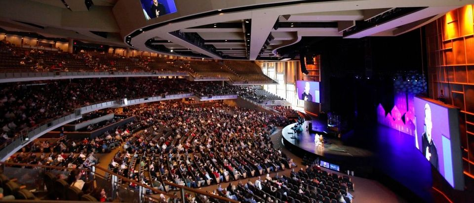 Pastor Gene Appel's image can be seen projected on several televisions in the 7,000-seat Willow Creek Community church during a Sunday service in South Barrington, Illinois, November 20, 2005. Institutions like Willow Creek and Houston's Lakewood Church, each drawing 20,000 or more on a weekend, offer not just a vast, shared attraction but a path that tries to link individuals on a faith-sustaining one-to-one level beyond the crowd, observers and worshipers say. Picture taken November 20, 2005. To match feature Religion Megachurches. REUTERS/John Gress