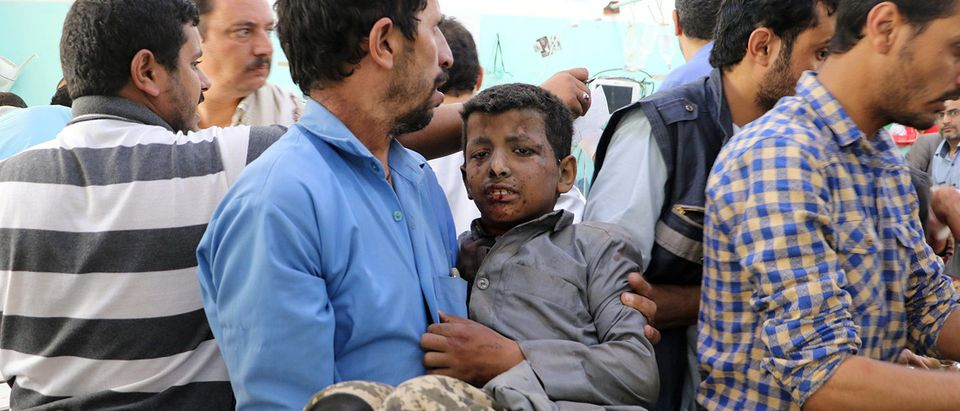 A Yemeni man holds a boy who was injured by an airstrike in Saada