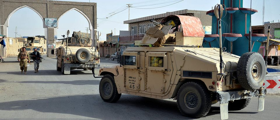 Afghan security guards walk during a Taliban attack in Ghazni city, Afghanistan