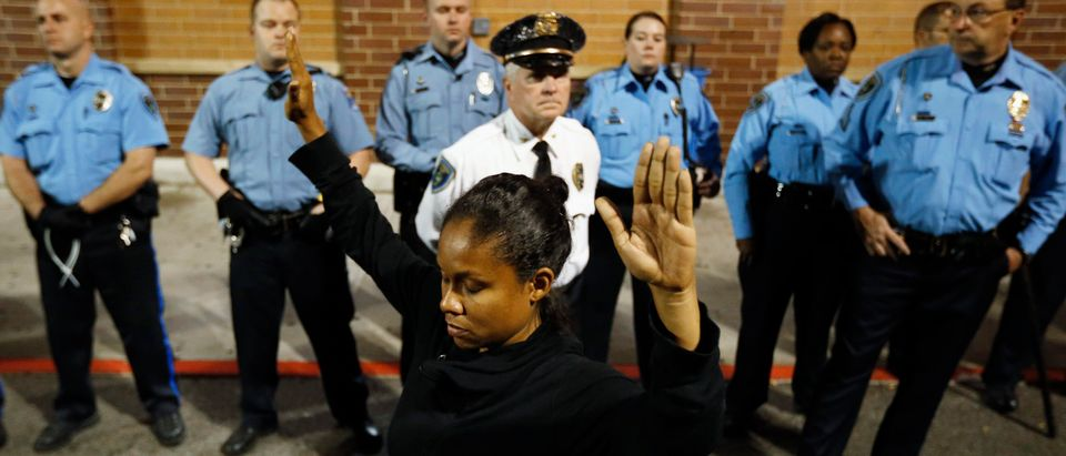 A protester demonstrates in front of police officers during a demonstration at a Walmart store in St. Louis, Missouri, October 13, 2014. Hundreds of people demonstrated in the pouring rain in the St. Louis area on Monday, staging a series of rolling protests in the latest show of anger over the police killing of an unarmed black teenager in August. At least 50 protesters were arrested in civil disobedience acts in Ferguson, the suburb where Michael Brown, 18, was shot dead. Other groups occupied St. Louis city hall, where they tried to hang a banner, shut down a local Walmart, and chanted outside a fundraiser for a local politician. REUTERS/Jim Young