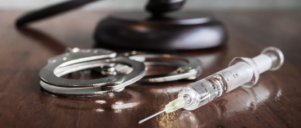 Handcuffs and a syringe rest near a gavel. Shutterstock image via user Nixx Photography
