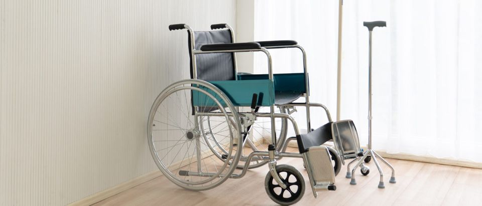 A wheelchair sits in a well-lit room. Shutterstock image via user Poommipat T