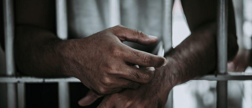 A man stands behind bars. Shutterstock image via kittirat roekburi