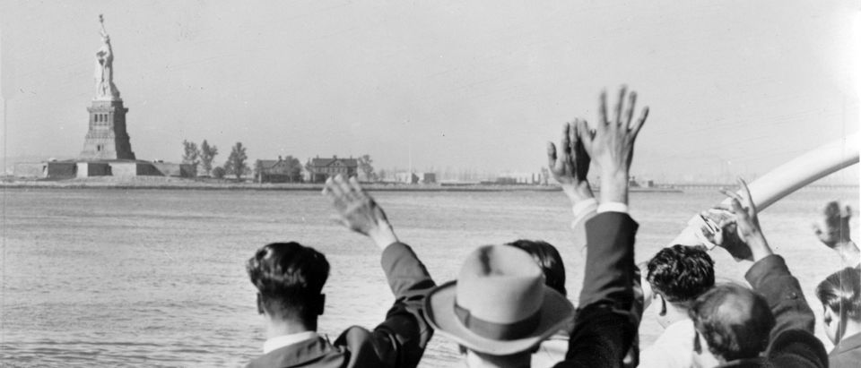 Part of a group of 171 illegal immigrants wave goodbye to Statue of Liberty from Coast Guard cutter that took them from Ellis Island to the Home Lines ship Argentina in Hoboken for deportation. 1952, Shutterstock/ By Everett Historical