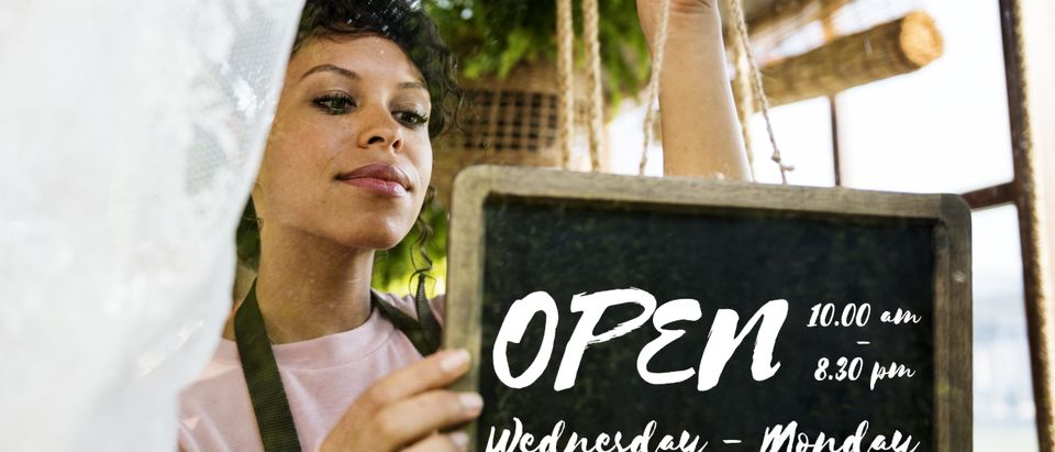 Store opener puts up sign, Shutterstock/ By Rawpixel.com