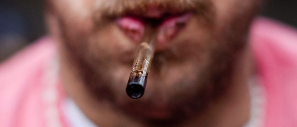 A man holds his used crack pipe in his mouth in Vancouver's DTES neighbourhood
