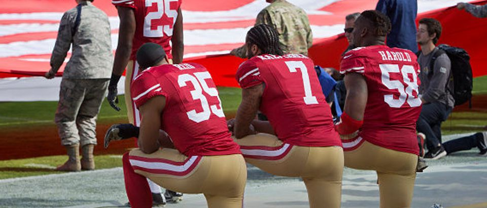 SANTA CLARA, CA - NOVEMBER 6: Quarterback Colin Kaepernick #7, safety Eric Reid #35, and linebacker Eli Harold #58 of the San Francisco 49ers kneel before a game against the New Orleans Saints with the U.S. flag unfurled in honor of the armed services on November, 6 2016 at Levi's Stadium in Santa Clara, California. The Saints won 41-23