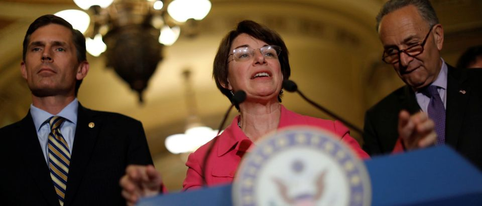 Senator Amy Klobuchar (D-MN), accompanied by Senate Minority Leader Chuck Schumer and Senator Martin Heinrich (D-NM), speaks with the media about the recently withdrawn healthcare bill on Capitol Hill in Washington, U.S., July 18, 2017. REUTERS/Aaron P. Bernstein