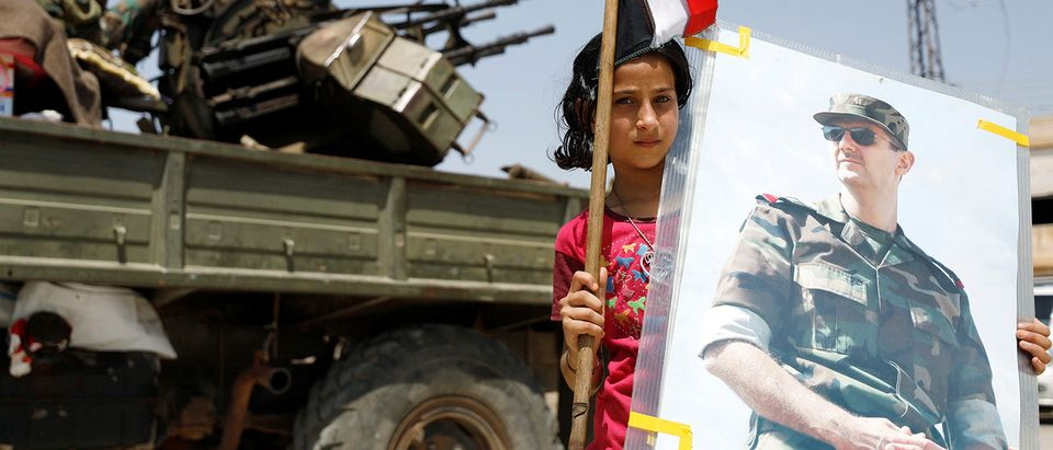A girl holds a Syrian flag and a picture of Syrian President Bashar al-Assad in Deraa