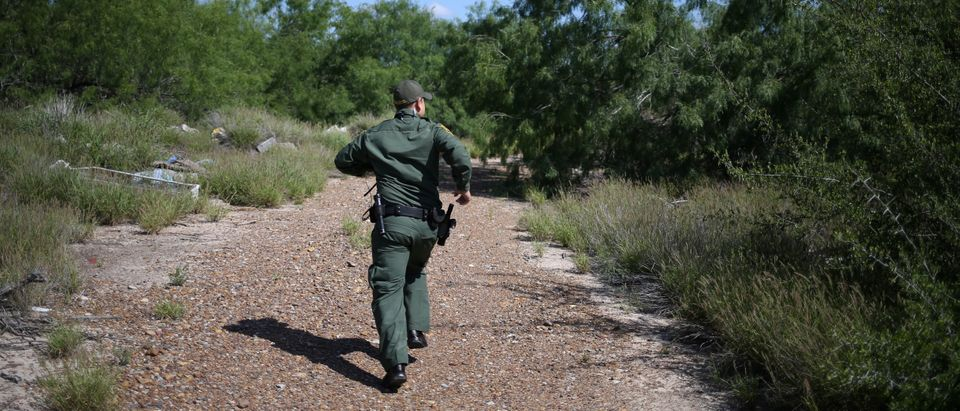 A U.S. Border Patrol agent and Air and Marine Operations helicopter pursue a man who illegally crossed the Mexico-U.S. border near McAllen
