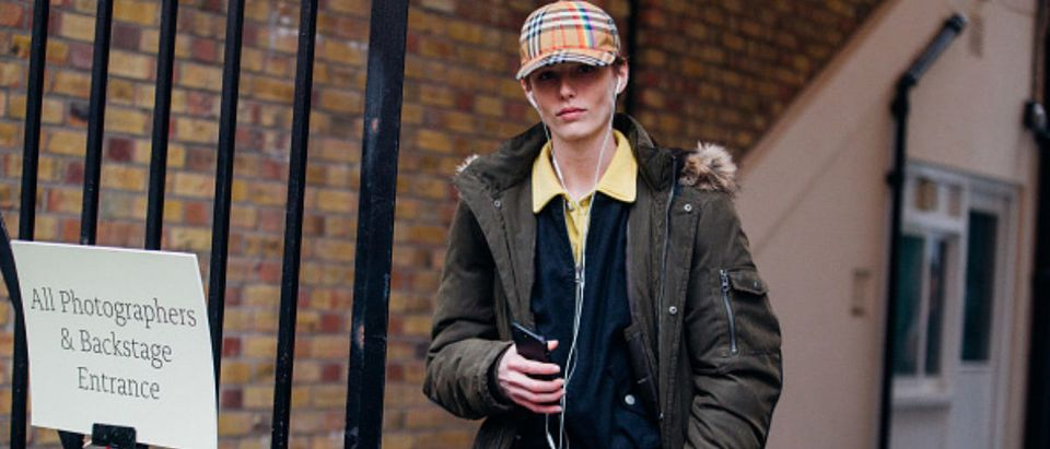 LONDON, ENGLAND - FEBRUARY 19: Model Emily Gafford listens to music with headphones and wears a Burberry tartan cap, a green coat, a yellow polo shirt under a blue jacket, and black Champion sweatpants, with Lucas luggage during London Fashion Week February 2018 on February 19, 2018 in London, England. (Photo by Melodie Jeng/Getty Images)