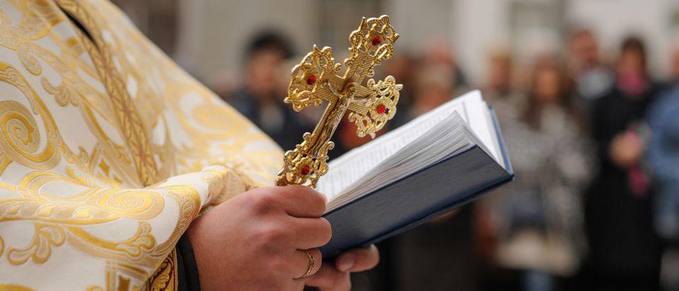Catholic Priest leading Mass (Shutterstock/Bogdan Mendrun)