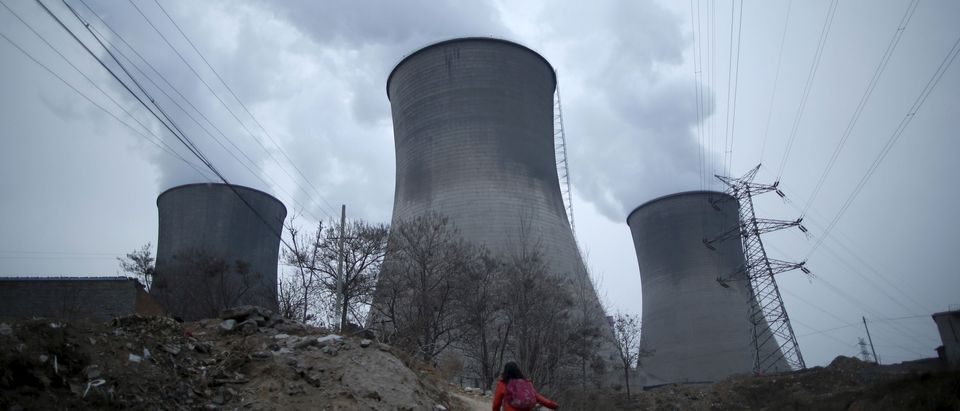 A girl makes her way to her house which locates next to cooling towers of coal-fired power plant in Shijiazhuang, Hebei province, China, January 28, 2015. Beijing introduced tougher regulations this year to combat pollution, keen to overhaul China's unwanted image of smog-choked cities, fouled waterways and heavy-metal tainted soil. Picture taken on January 28, 2015. REUTERS/Kim Kyung-Hoon -