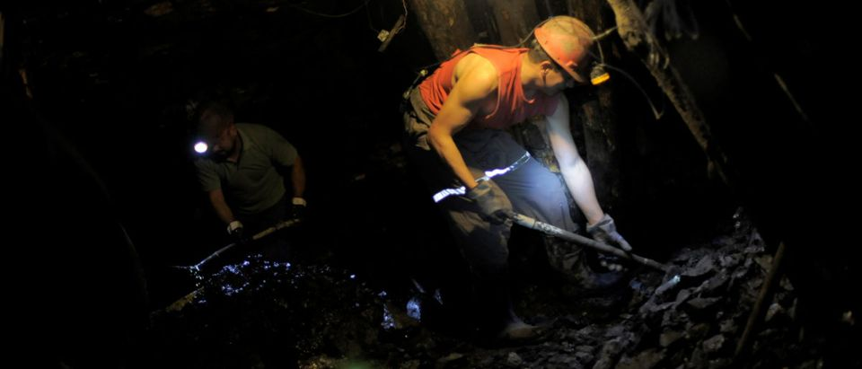 "Coal miners use shovels to remove coal from inside an old artisanal coal mine, so called ""Pique"", in Curanilahue"