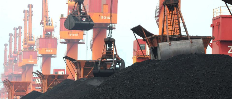 Imported coal is seen lifted by cranes from a coal cargo ship at a port in Lianyungang, Jiangsu