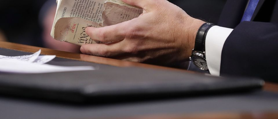 WASHINGTON, DC - SEPTEMBER 05: Supreme Court nominee Judge Brett Kavanaugh thumbs through a well-worn, pocket-sized copy of the U.S. Constitution as he testifies before the Senate Judiciary Committee on the second day of his confirmation hearing on Capitol Hill September 5, 2018 in Washington, DC. Kavanaugh was nominated by President Donald Trump to fill the vacancy on the court left by retiring Associate Justice Anthony Kennedy. (Photo by Chip Somodevilla/Getty Images)