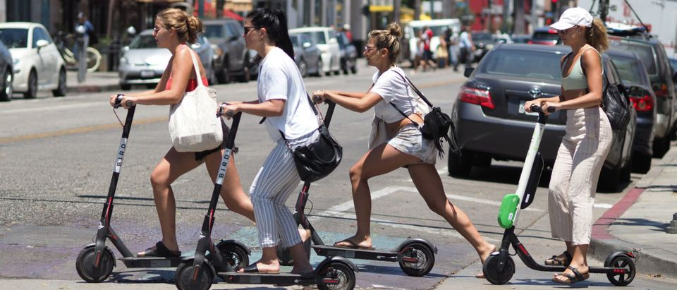 Young women ride shared electric scooters in Santa Monica, California, on July 13, 2018. ROBYN BECK/AFP/Getty Images