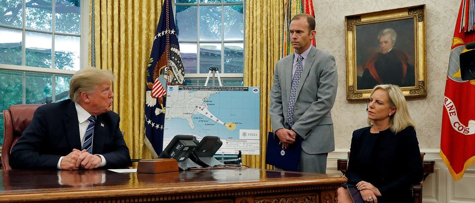 U.S. President Donald Trump asks FEMA Administrator Brock Long a question during an Oval Office meeting on preparations for hurricane Florence as U.S. Homeland Security Secretary Kirstjen Nielsen sits at right at the White House in Washington