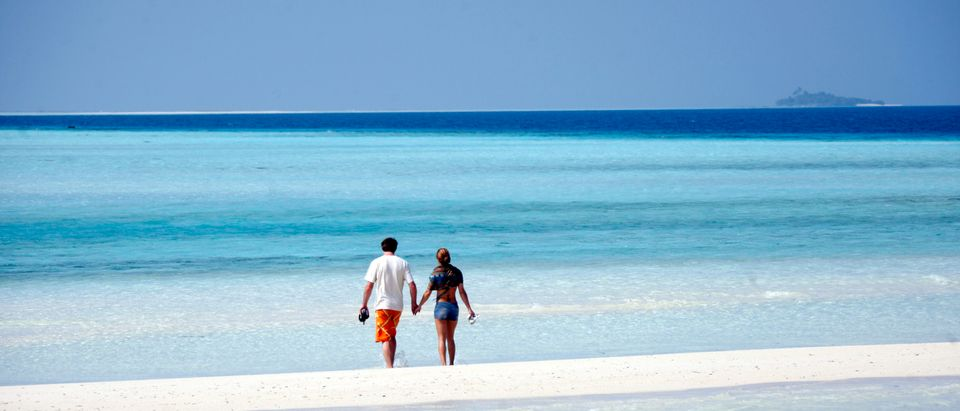 General view shows tourists on the sandy beach of Olhuveli island in Maldives