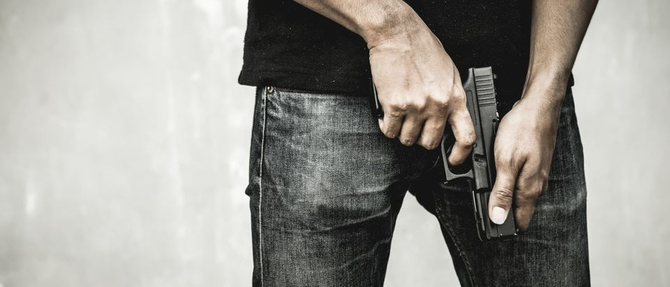 Man holding a gun (Shutterstock/BR Photo Addicted)