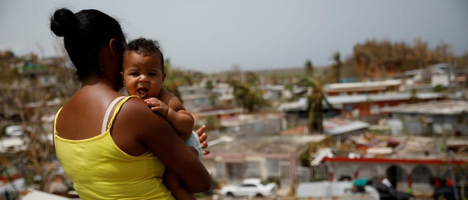 Ysamar Figueroa carrying her son Saniel, looks at the damage in the neighbourhood after the area was hit by Hurricane Maria, in Canovanas