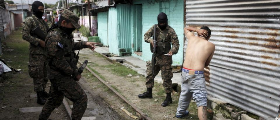 Army soldiers interrogates a suspected gang member during a patrol operation after residents flee the Amaya Community, due to threats from suspected gang members, in San Salvador, October 13, 2015. Around 10 families were threatened with death by suspected members of the MS 13 gang if they do not leave their houses. Many in El Salvador have been displaced from their homes due to gang-related threats, according to local media. REUTERS/Jose Cabezas