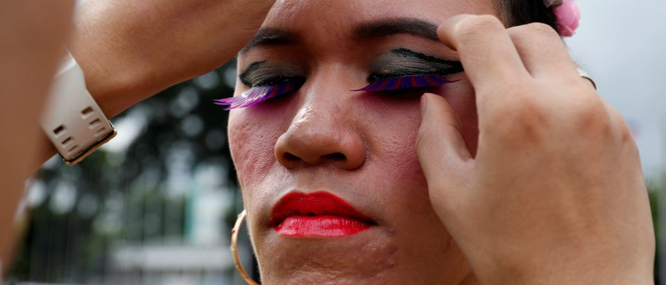 A colleague fixes an eyelashes of a transgender person before the start of a Gay Pride parade in Marikina
