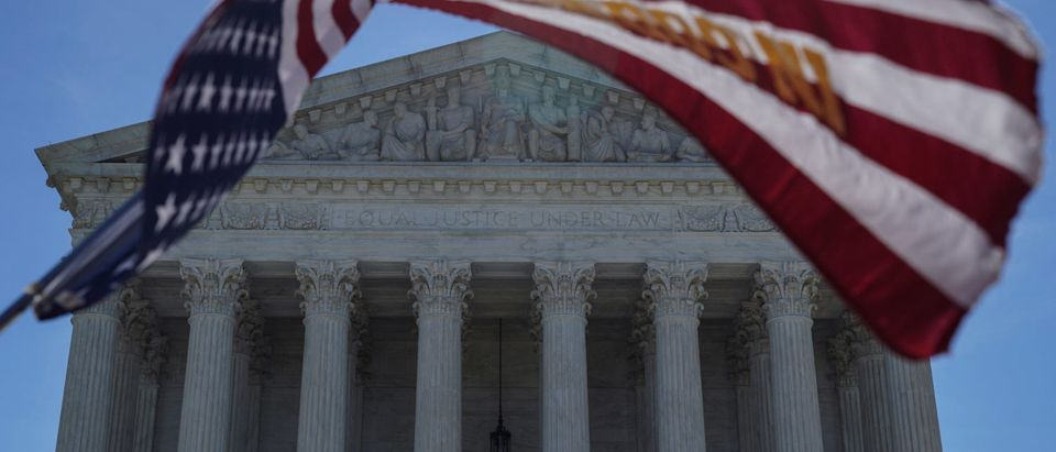 A man holds a flag outside the U.S. Supreme Court, as the Trump v. Hawaii case regarding travel restrictions in the U.S. remains pending, in Washington, U.S., June 25, 2018. REUTERS/Toya Sarno Jordan