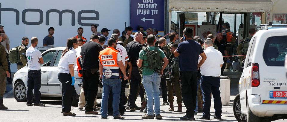 Israeli security personnel and medics work at the scene of a stabbing attack near a mall in the Gush Etzion Junction in the occupied West Bank