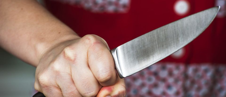 Pictured is a woman holding a knife. (Shutterstock/ Paul Biryukov)
