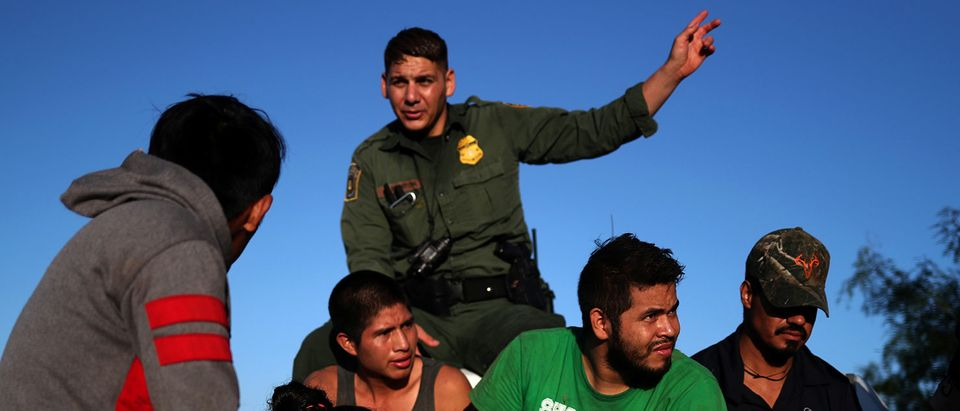 Men and a woman are apprehended by the Border Patrol in Falfurrias, Texas after thye illegally crossed into the U.S. border from Mexico