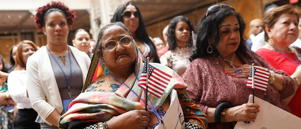 New citizens stand during a U.S. Citizenship and Immigration Services (USCIS) naturalization ceremony at the New York Public Library in Manhattan
