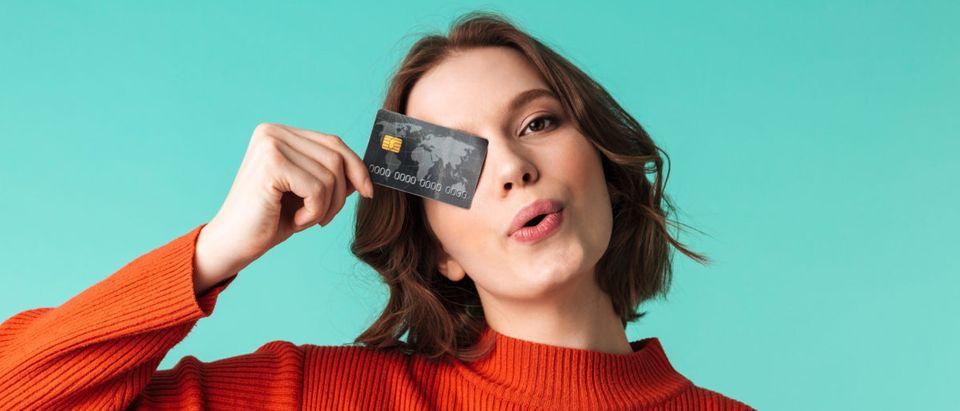 A woman holds a credit card. Shutterstock image via user Dean Drobot