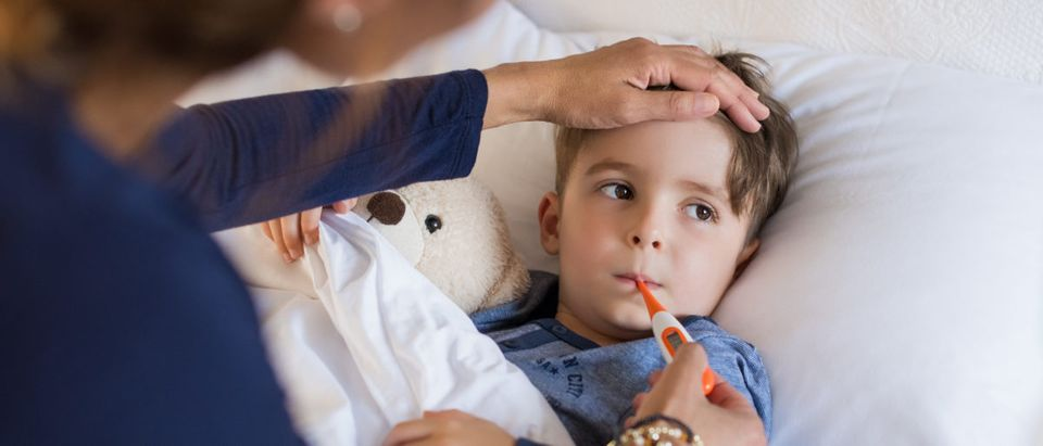 A boy lays in bed with a fever. Shutterstock image via user Rido