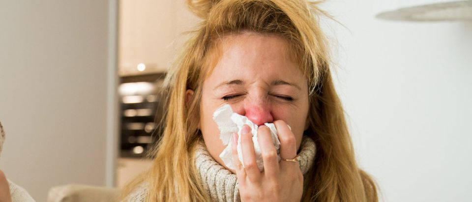 A woman is sick with the flu. Shutterstock image via user Aleksandra Suzi